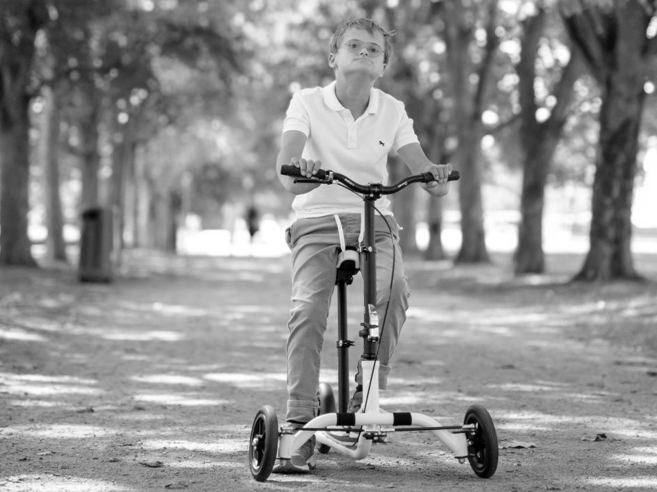 Kid rides mobility aids bike